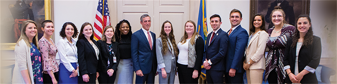 Students on a public policy assistanship as legislative fellows stand with Governor John Carney.