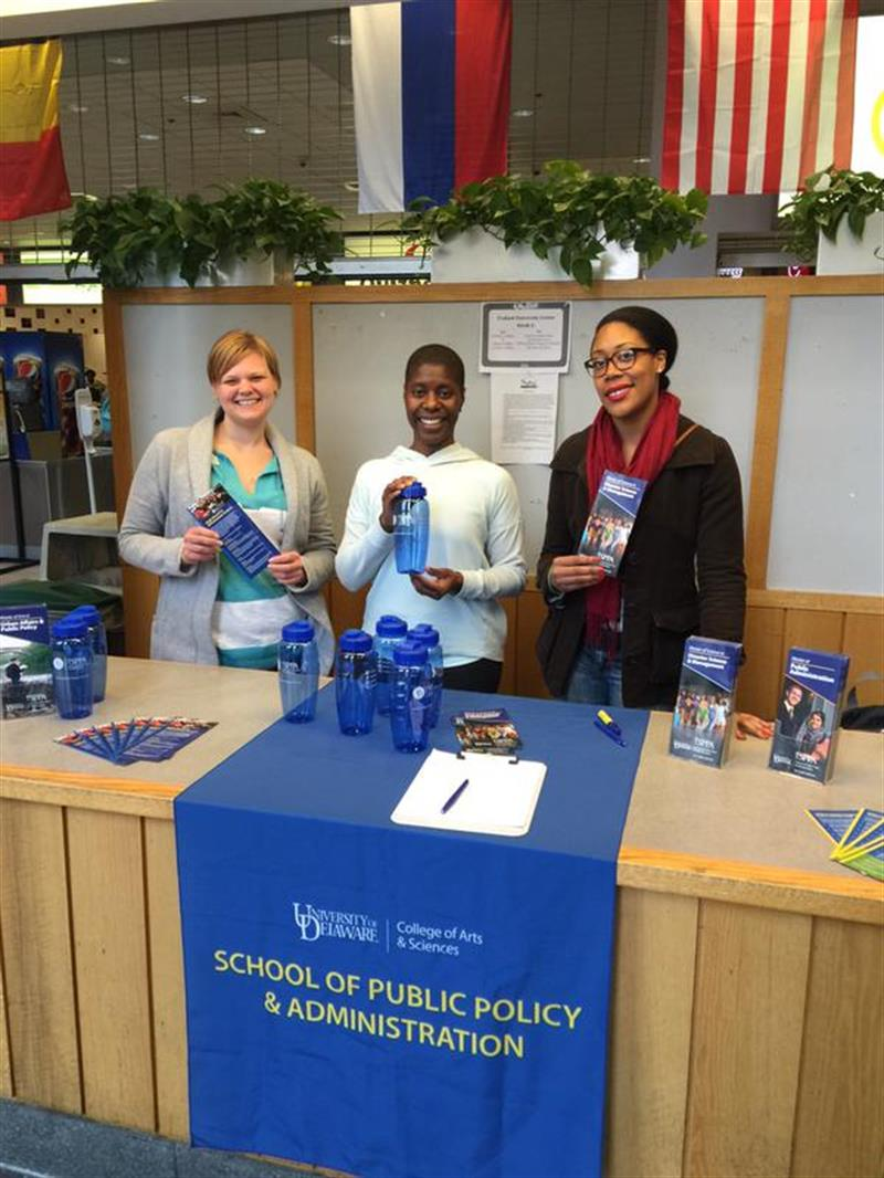 Three graduate students in the school hand out water bottles and brochures at a promotional table.