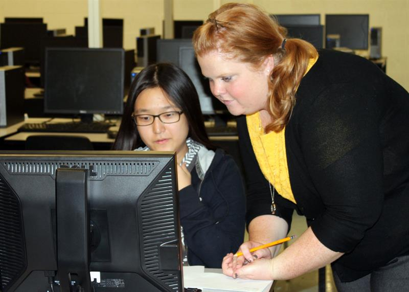 A graduate research assistant helps a high school student apply to college during an Institue for Public Administration project.