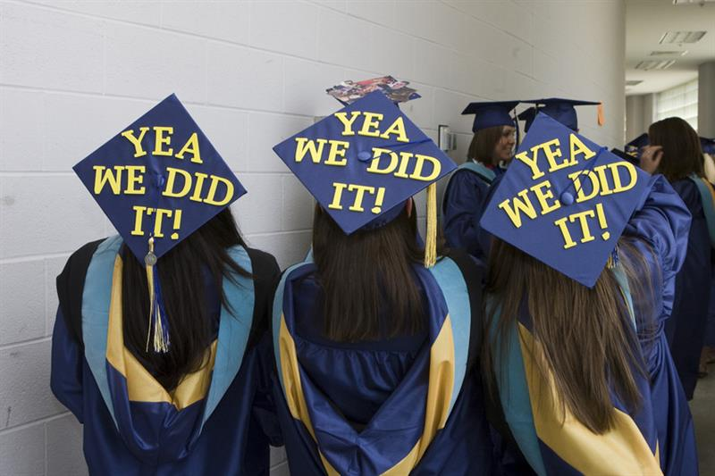 "Students wear graduation caps that say ""Yea We Did It!"""