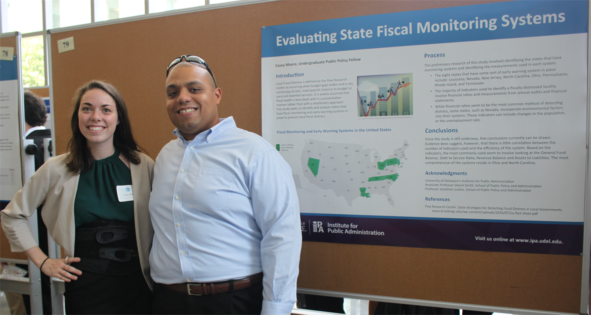 "Student Casey Moore with MPA Program Director Dan Smith with their poster presentation, ""Evaluating State Fiscal Monitoring Systems."""