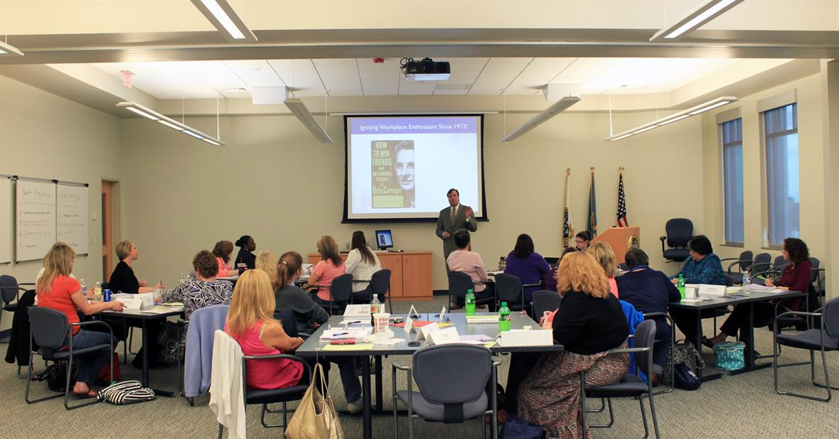 Training program participants watch a slideshow presentation called Igniting Workplace Enthusiasm.