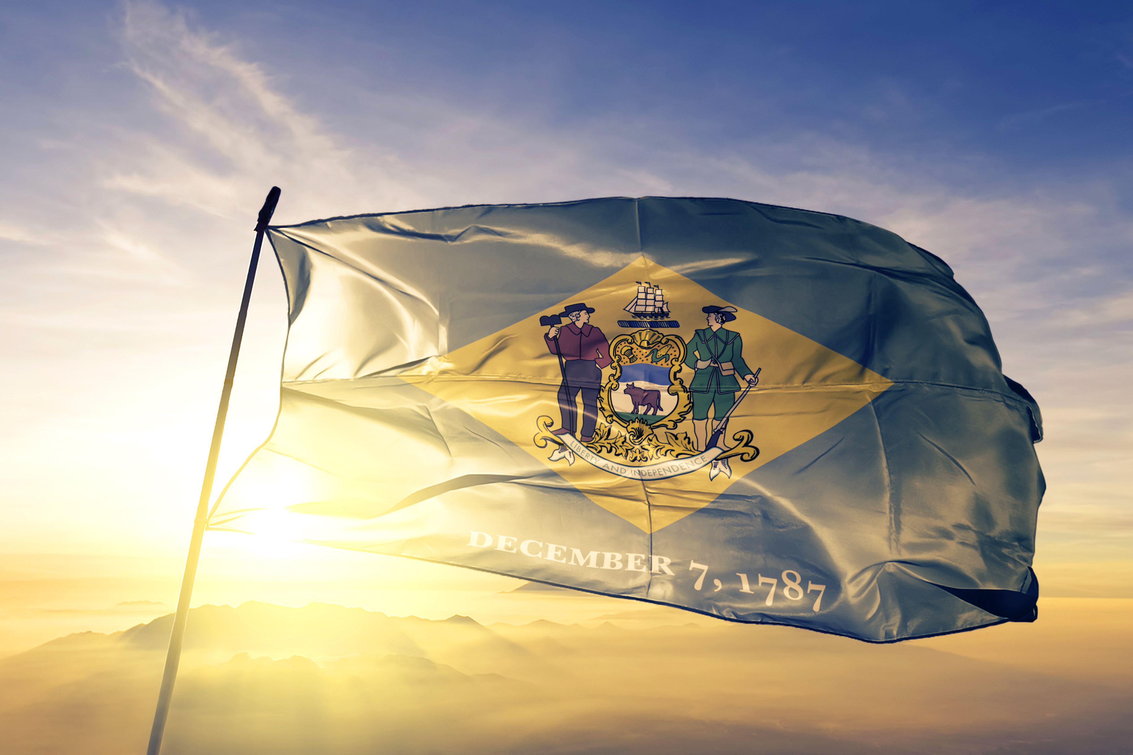 State of Delaware Flag flying in the sky as the sun rises