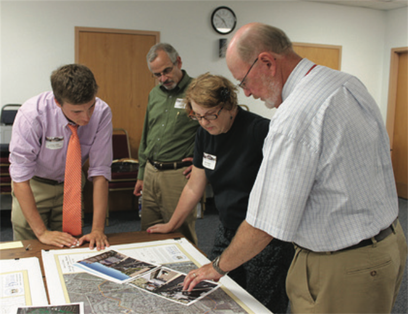 Two IPA Regional Development and Planning Team members review town planning materials with city administrators to develop and update city code and zoning ordinances.