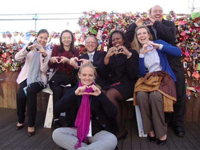 A group of students studying abroad in Seoul make hearts with their hands.