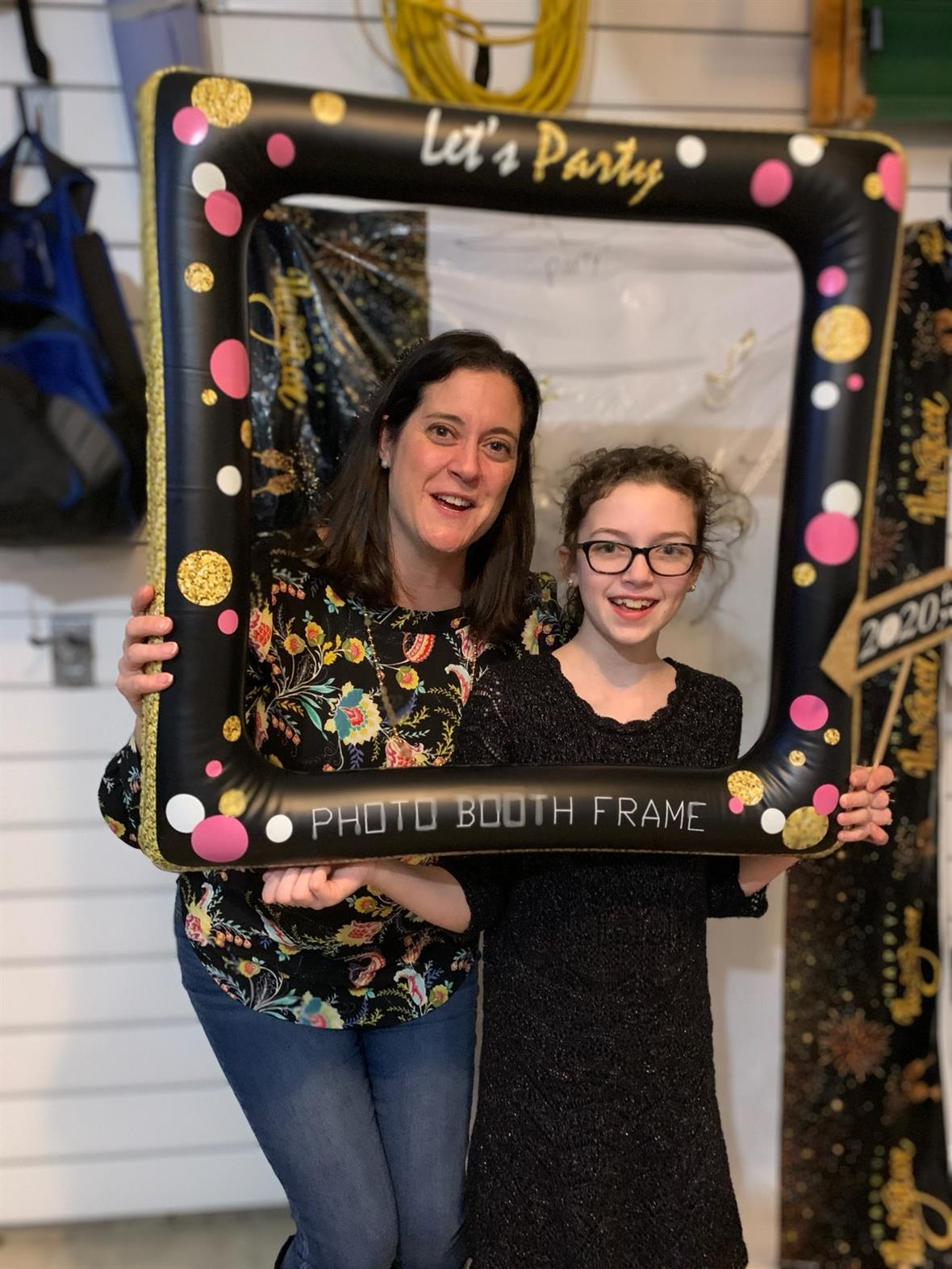 Kelly and Izzy Sherretz pose for a photo with an inflatable photo frame.